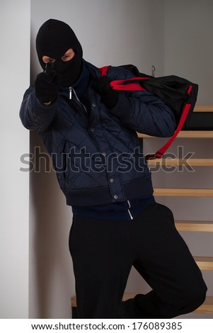 A masked robber with bag aiming at you - stock photo