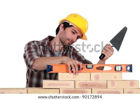 A mason using  a level to check his wall. - stock photo