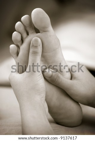 A massage therapist doing reflexology foot massage on a patient's foot - stock photo