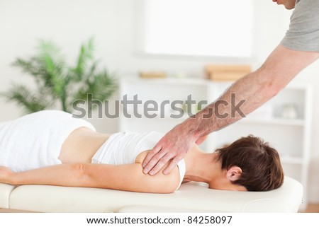 A masseur is massaging a woman's back in his surgery - stock photo