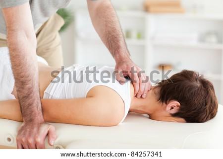 A masseur is massaging a woman's neck - stock photo