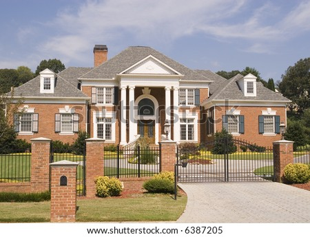 A massive brick house behind a brick and iron fence - stock photo