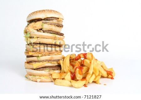 A massive burger with fries covered in ketchup - stock photo