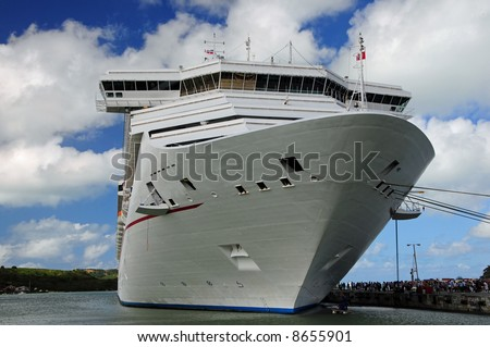 A massive cruise ship is anchored at the pier - stock photo