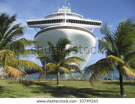 A massive cruise ship is shown framed by palm trees - stock photo