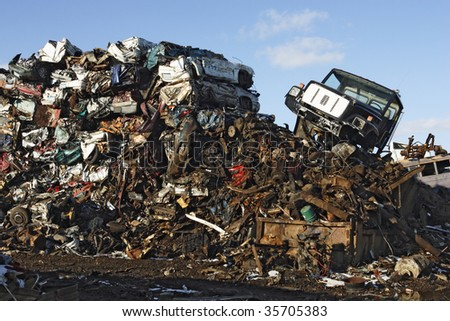 A massive pile of crushed cars at a junkyard.