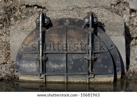 a massive pivoting iron hatch at the end of a drain pipe blocking  back flow from a river - stock photo