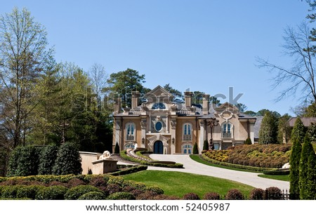 A massive stucco mansion atop a professionally landscaped hill - stock photo