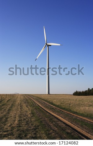 A massive wind turbine towers over a rural landscape.