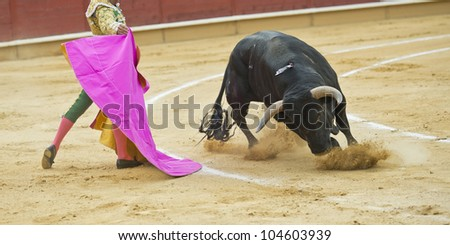 A matador fighting in a typical Spanish bullfight. - stock photo