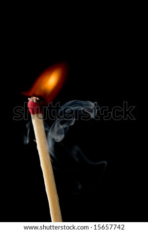 A match just beginning to ignite and smoke. - stock photo