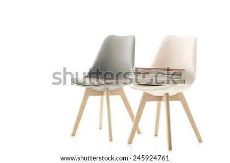 A matching stylish grey and white modern molded chair with wooden legs standing side by side with a pile of books on one seat over a white background with copyspace - stock photo