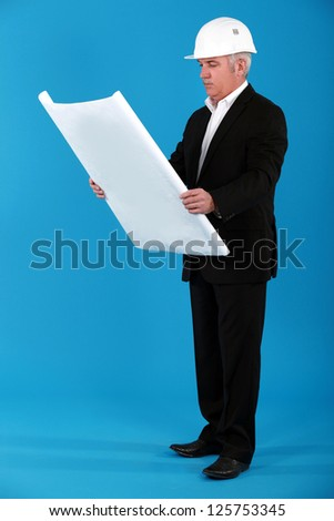 A mature architect checking his blueprint. - stock photo
