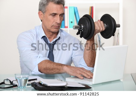 A mature businessman lifting weights in his office. - stock photo