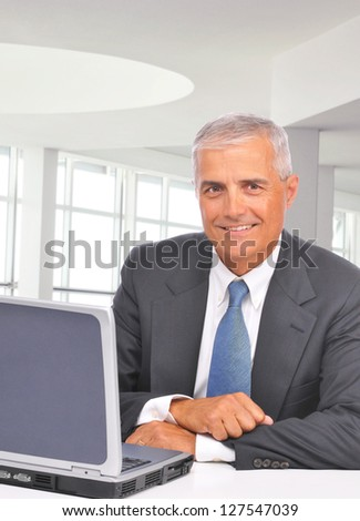 A mature businessman sitting at his desk in a modern office with laptop. Man is smiling at the camera. Vertical format. - stock photo