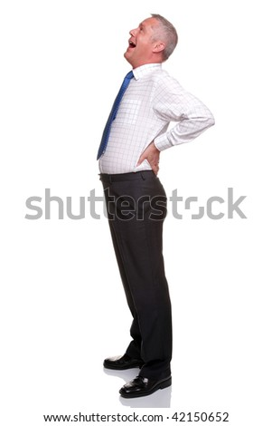 A mature businessman with his hands on his hips as he yawns, isolated on a white background. - stock photo