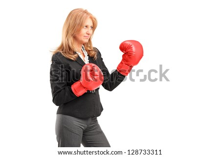A mature businesswoman with red boxing gloves ready to fight isolated on white background - stock photo