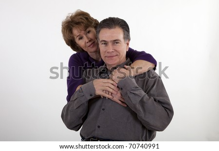 A mature couple affectionately hold each other and smile for the camera.