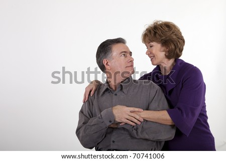 A mature couple affectionately hold each other and smile lovingly at one another.
