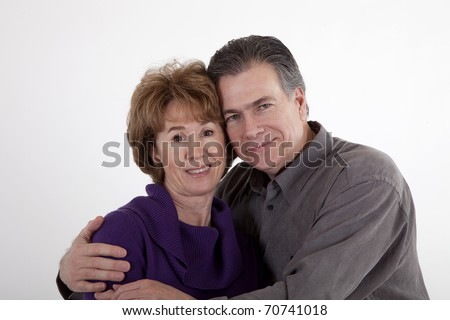 A mature couple affectionately hug each other and smile for the camera.