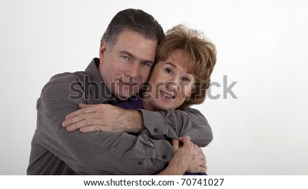 A mature couple in a playful embrace smile for the camera.
