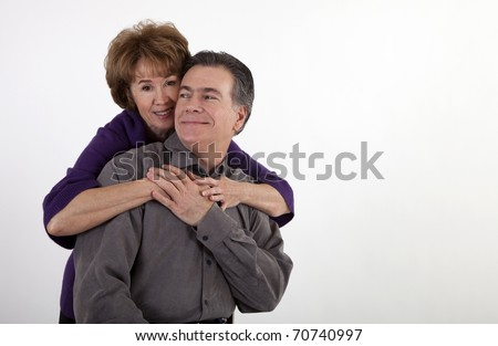 A mature couple in a playful embrace smiling for the camera.