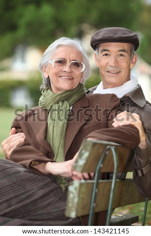 A mature couple on a bench. - stock photo