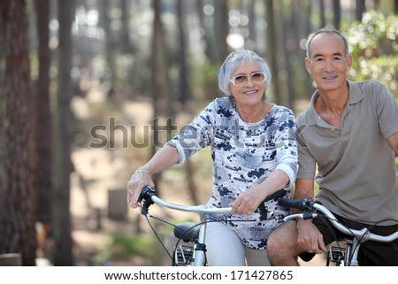 A mature couple on a bike ride. - stock photo