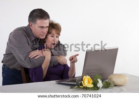 A mature couple read something the woman finds surprising on her laptop screen. - stock photo