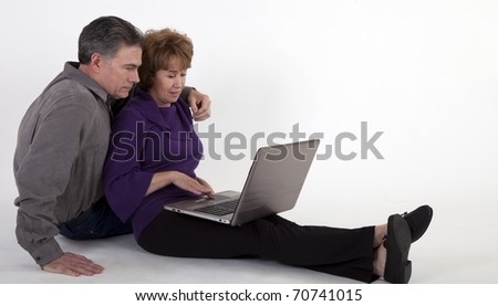 A mature couple sitting on a white backdrop looking at something on a laptop.