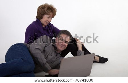 A mature couple with please expressions on their faces as if reading something pleasant on the a laptop screen.