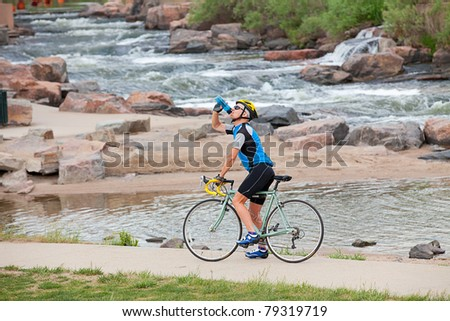 A mature cyclist takes a break by the river - stock photo