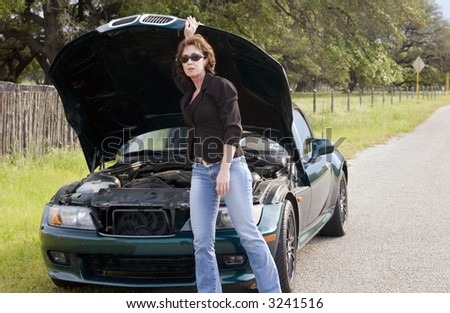 A mature distress woman standing in front of a vehicle that appears to be having some sort of mechanical failure. - stock photo