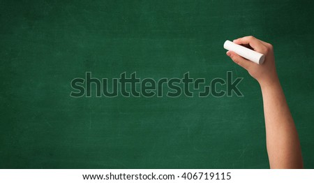 A mature hand writing or drawing on a clean green blackboard with a white chalk. - stock photo