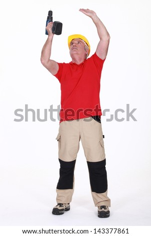 A mature handyman drilling the ceiling. - stock photo
