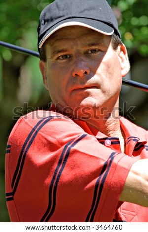 A mature male golfer finishing golf swing - portrait. - stock photo