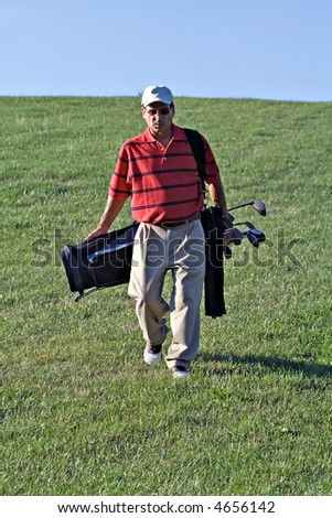 A mature male golfer walking the golf course carrying bag and clubs. - stock photo