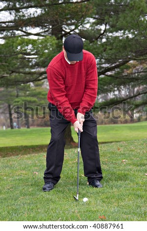 A mature male golfer wearing red sweater playing golf in autumn. - stock photo