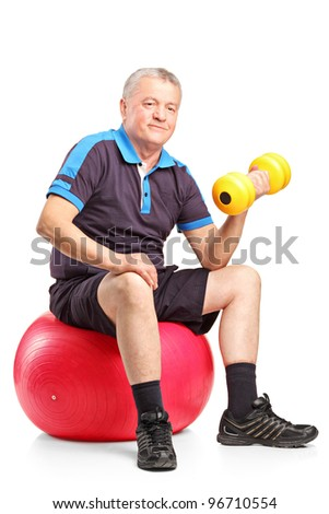 A mature man lifting up a dumbbell seated on a fitness ball isolated on white background - stock photo