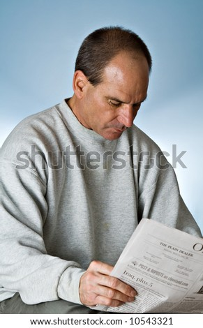 A mature man reading the daily newspaper. - stock photo