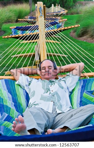 A mature man rests on a hammock while on vacation in South Carolina. - stock photo