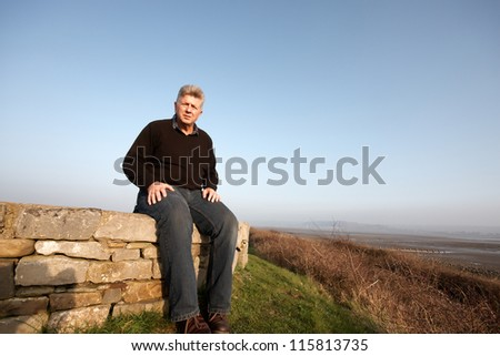 A mature man sitting on a wall with blue sky background - stock photo