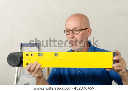 a mature man with a yellow spirit level - stock photo