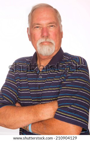 A mature man with his arms crossed and a serious expression on his face. - stock photo