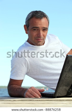 A mature man with his laptop by the seashore. - stock photo