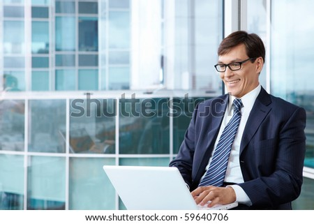 A mature man with laptop in the office - stock photo