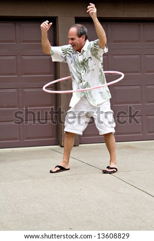 A mature man - 55 years old - plays with a hula hoop.