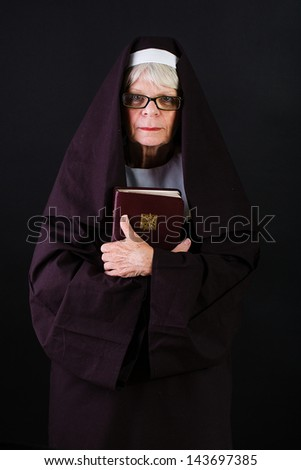 A mature nun holding a bible - stock photo