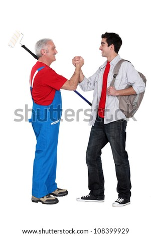 A mature painter shaking hand with his trainee. - stock photo