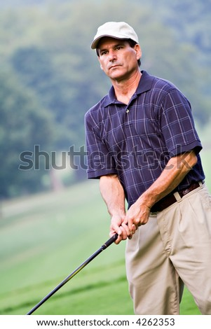 A mature rugged well-dressed golfer with serious express watching his last shot. - stock photo